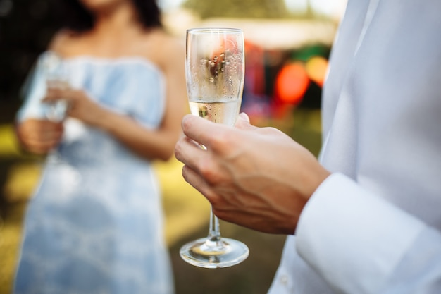 A man with a glass of champagne in his hands on a company of celebrating people. wedding, birthday, anniversary.