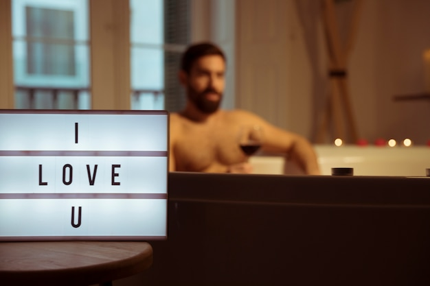 Man with glass of drink in spa tub and i love u title on lamp