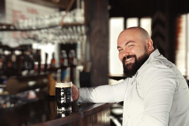 パブでビールのグラスを持つ男