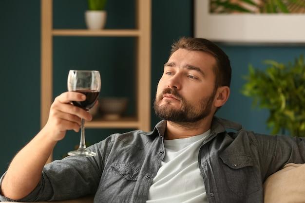 집에서 휴식을 취하는 와인 한 잔을 가진 남자