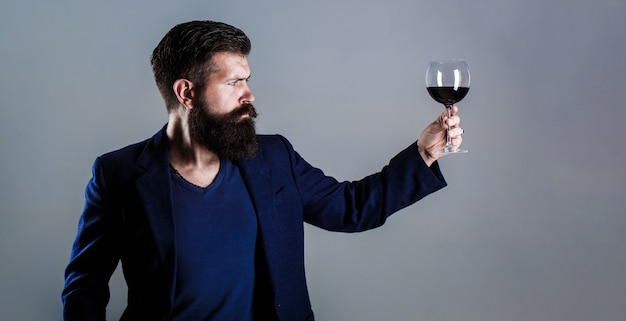 Man with a glass of red wine in his hands. beard man, bearded, sommelier tasting red wine. sommelier, degustator with glass of wine, winery, male winemaker.