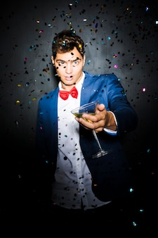 Man with glass between throwing confetti