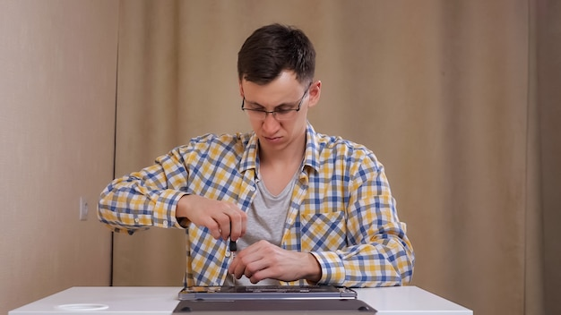 眼鏡をかけた男が白いテーブルに座ってラップトップを分解します