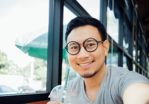 Man with glasses drinks coffee in the cafe