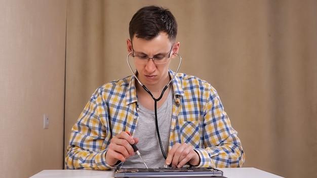 眼鏡をかけた男性は、分解されたラップトップを調べ、電話内視鏡で聞きます。