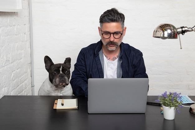 ワークスペースで一緒に座っている彼の犬と一緒に家から働くフリーランスの眼鏡の男