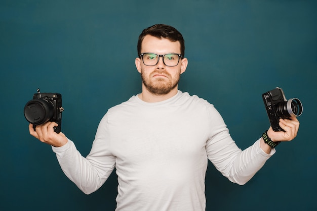 Man with glasses holding an old camera and a new camera and thinking about choosing which one