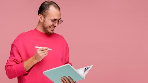 Человек в очках держит книгу и смеется