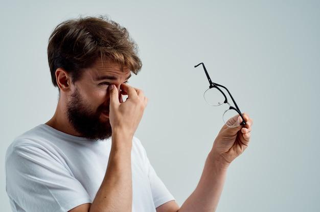 手に眼鏡をかけた男視力の問題のクローズアップ