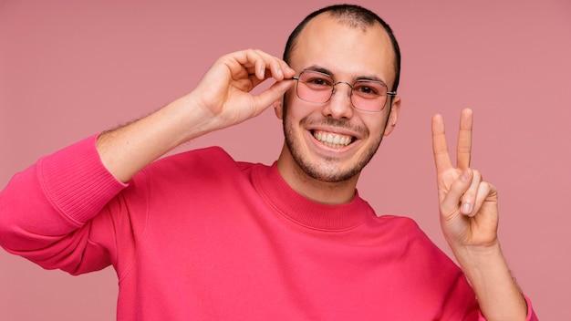Uomo con gli occhiali che ride e che mostra il segno di pace