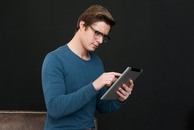 Man with glasses looking on tablet