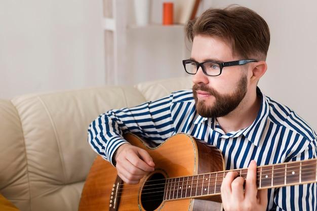 Uomo con gli occhiali a suonare la chitarra a casa