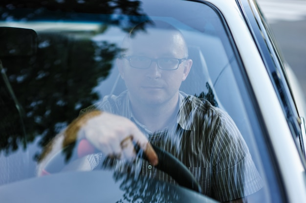 Man with glasses sitting behind the wheel of a car