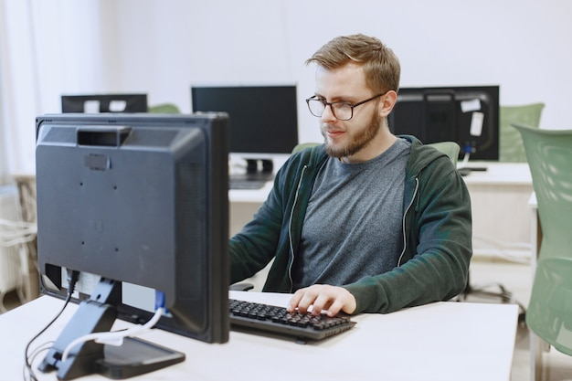 L'uomo con gli occhiali. studente in classe di informatica. la persona usa un computer.