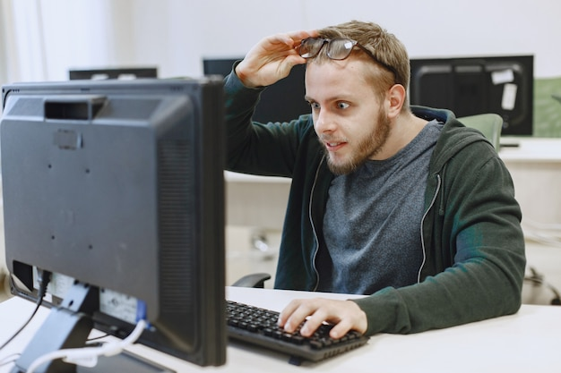 Man with the glasses. student in computer science class. person uses a computer.