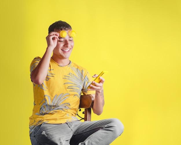 Человек в очках удивлен, читая сообщение на своем мобильном телефоне, сидя на стуле