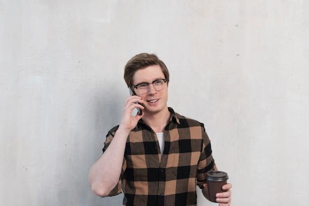 Uomo con gli occhiali a parlare sul suo telefono