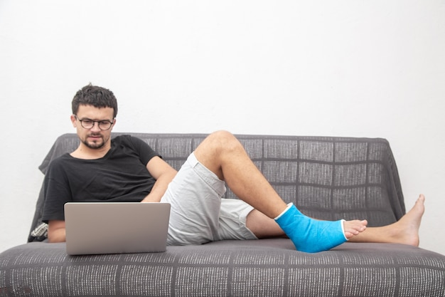 Man with glasses with broken leg in blue splint for treatment of injuries from ankle sprain working on a laptop on couch at home.
