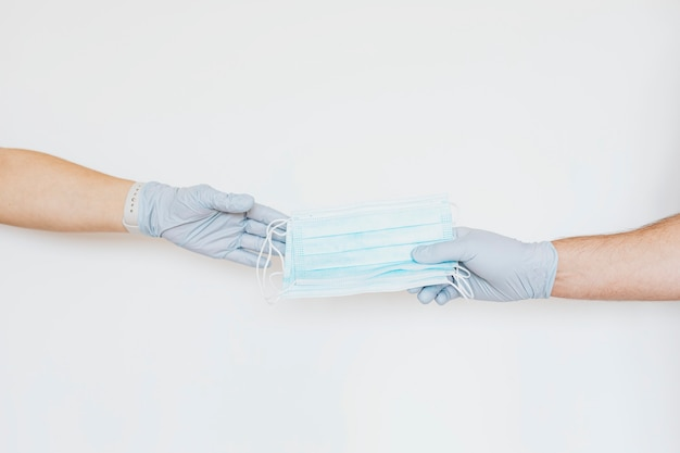 Man with a glove sharing a face mask to a friend on a gray background