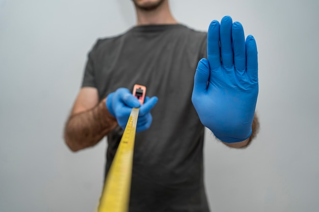 Man with gloves holding tape measurer for social distancing