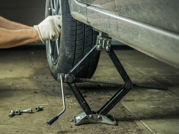 A man with gloves on repairing the rear wheel of the car.