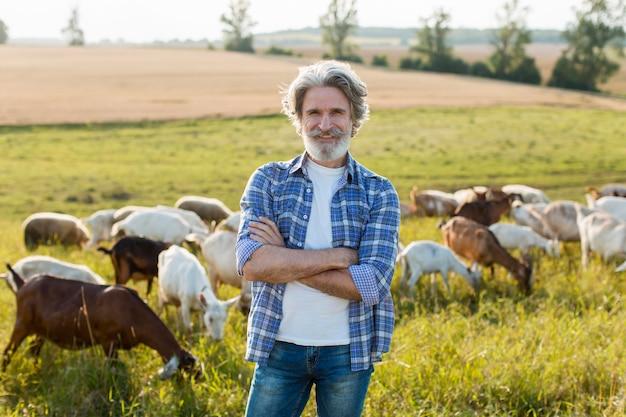 農場でヤギを持つ男