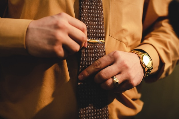 Man with a gold watch adjusts a tie