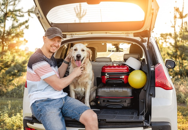 Man with golden retriever sitting in open car trunk next to luggage