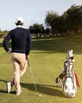 Человек с клюшками для гольфа на поле