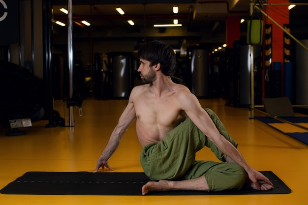A man with a good body does yoga in the gym. the concept of a healthy lifestyle and body's capabilities