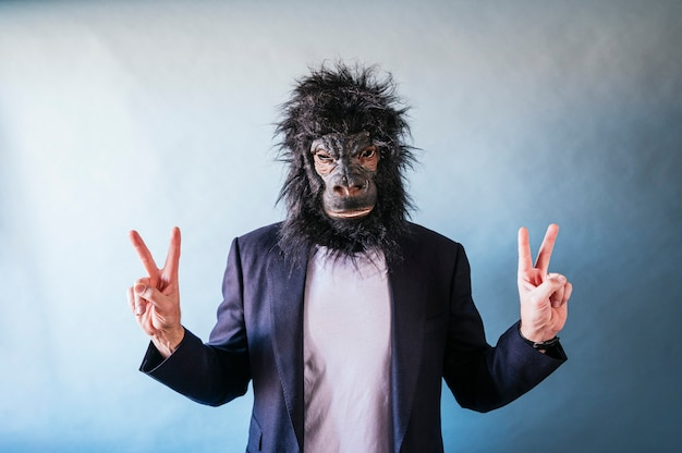 Man with gorilla mask posing and showing fingers in v symbol