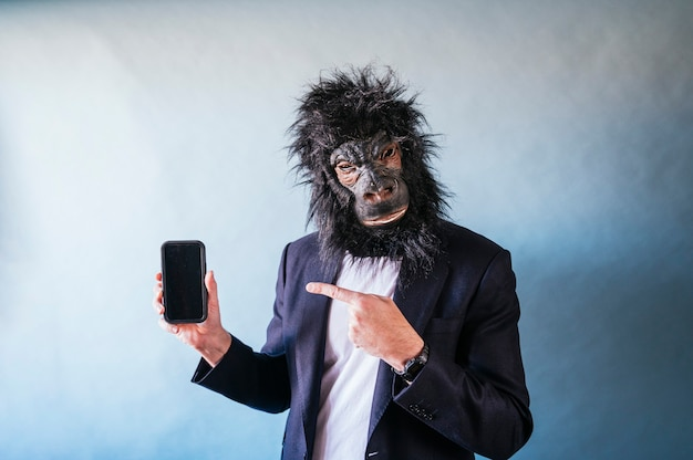 Man with gorilla mask showing smartphone