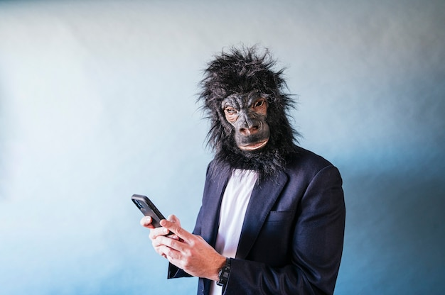 Man with gorilla mask using smartphone