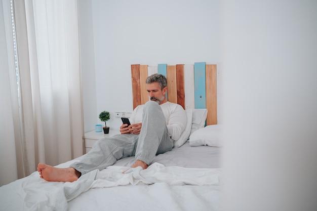 침대에 누워 일어날 때 전화기를 바라보는 50대 백발의 남자