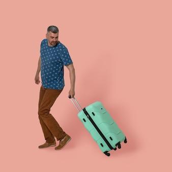 Человек с зеленым пластиковым чемоданом позирует в студии на розовом