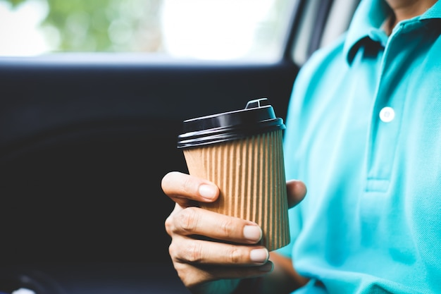 A man with green shirt holding a cup of coffee in the car.