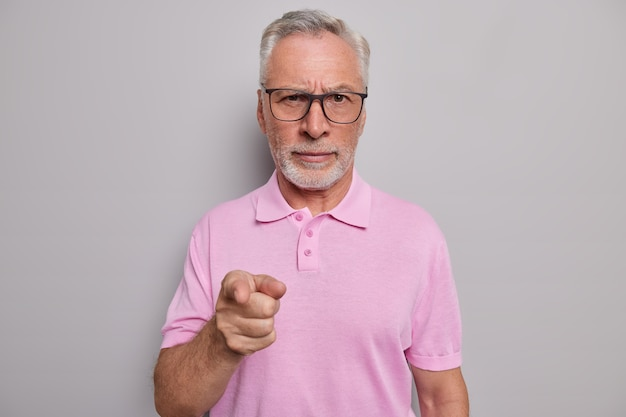 Man with grey beard points index finger forward asks to help him wears spectacles for good vision casual pink t shirt isolated on grey studio