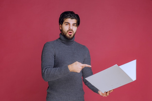 Man with grey folder discussing it with the colleagues while checking.