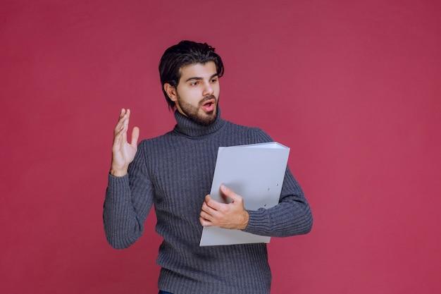 확인하는 동안 동료와 함께 논의하는 회색 폴더를 가진 남자.