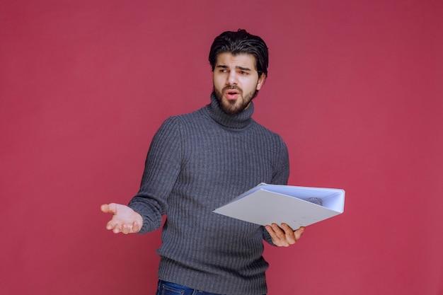 チェックしながら同僚とそれを議論する灰色のフォルダを持つ男。 無料写真