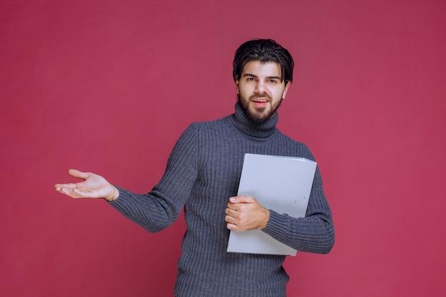 チェックしながら同僚とそれを議論する灰色のフォルダを持つ男。