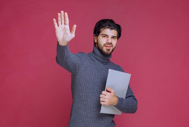 灰色のフォルダーの挨拶と握手を持つ男。