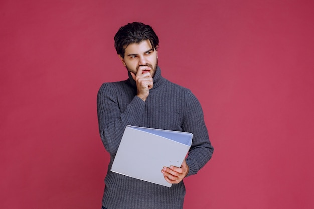 Man with grey folder looks thoughtful.