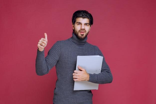 灰色のフォルダーを持つ男は、楽しみの手サインを作ります。