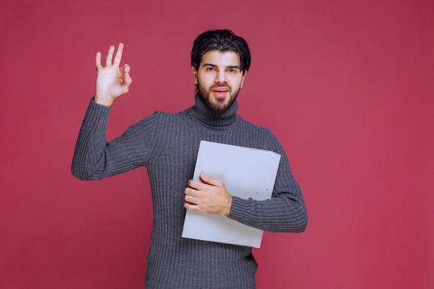 회색 폴더를 가진 남자는 즐거움 손 기호를 만든다.