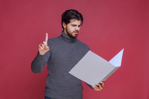 L'uomo con la cartella grigia fa il suo dito puntato verso l'alto.