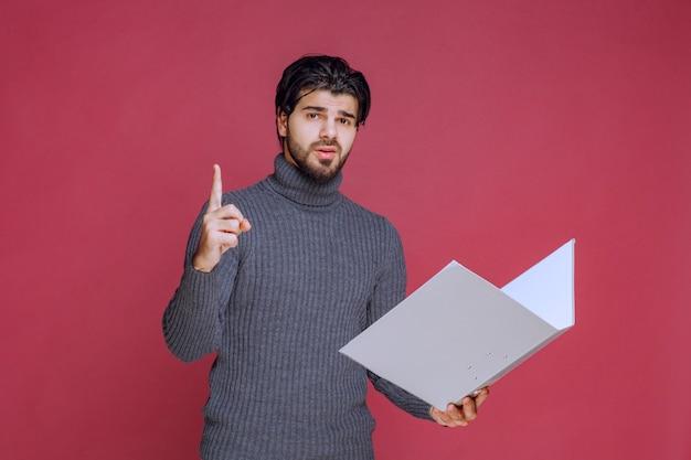 회색 폴더를 가진 남자는 그의 포인트 손가락을 만듭니다.
