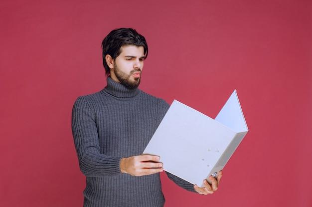 보고서를 읽는 회색 폴더를 가진 남자입니다.