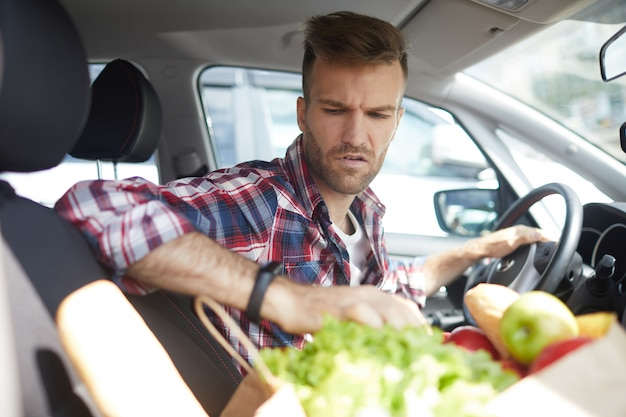 車の中で食料品を持つ男