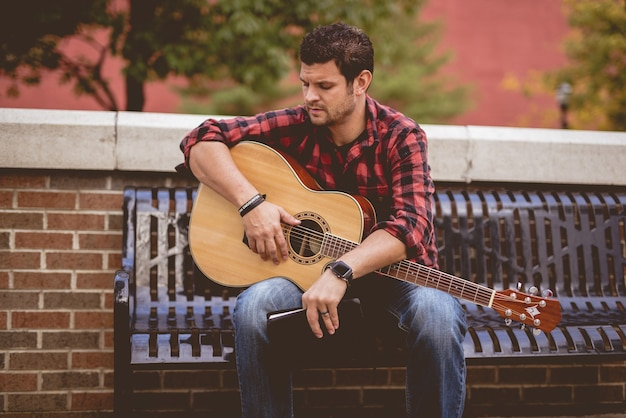 Uomo con una chitarra e un libro seduto su una panchina nel parco
